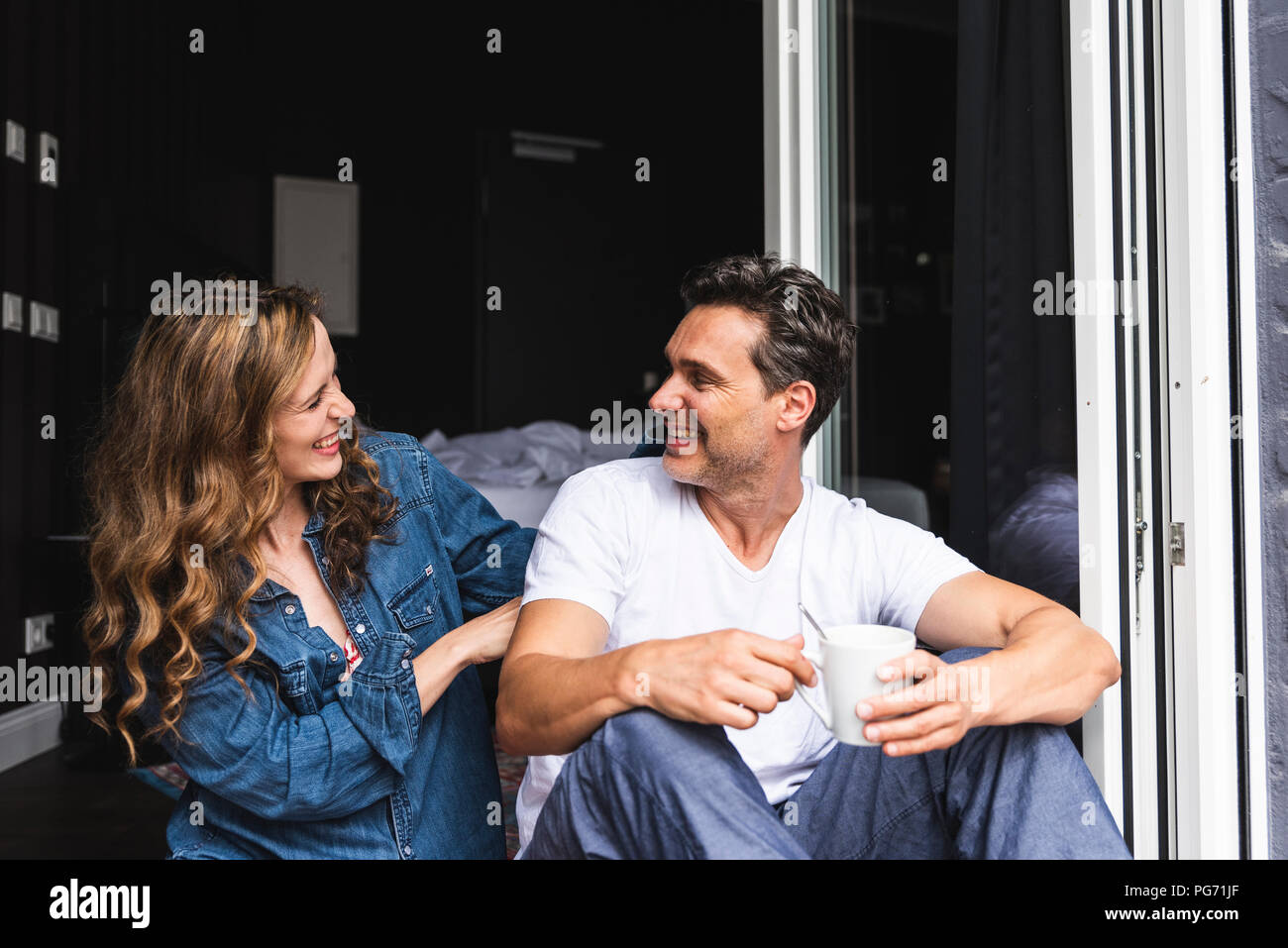 Happy couple in nightwear at home sitting at French window Stock Photo