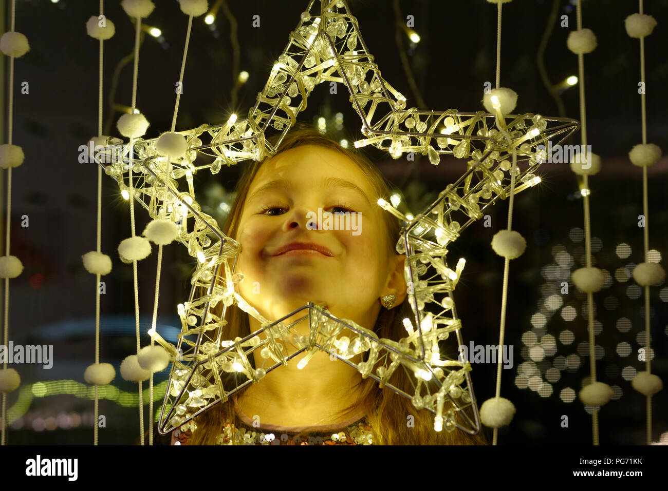 Portrait of smiling little girl looking through Christmas star - Stock Image