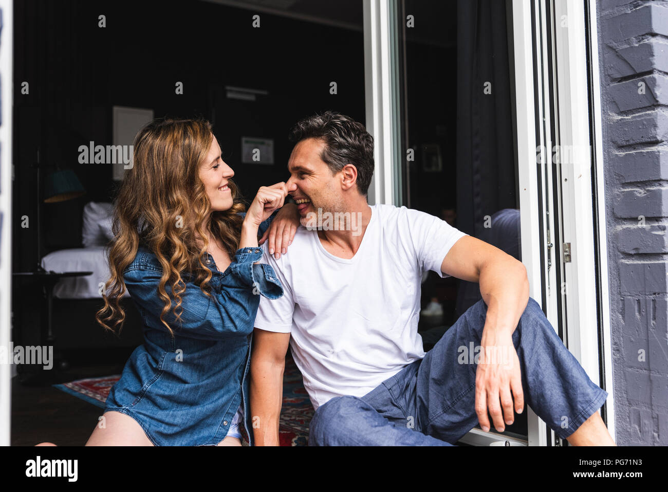 Playful couple in nightwear at home sitting at French window - Stock Image