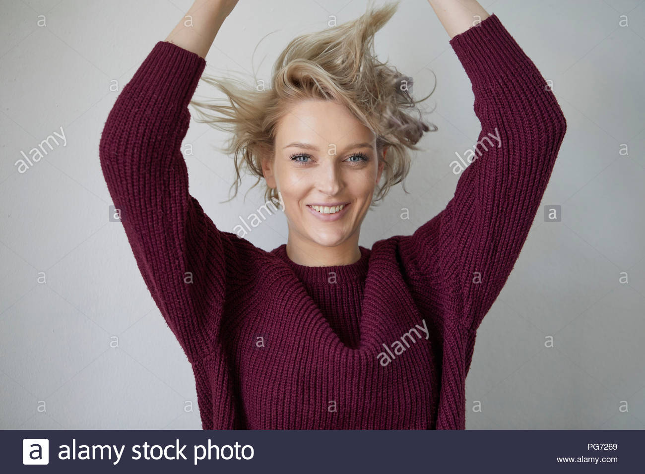 Portrait of smiling blond woman with tousled hair - Stock Image