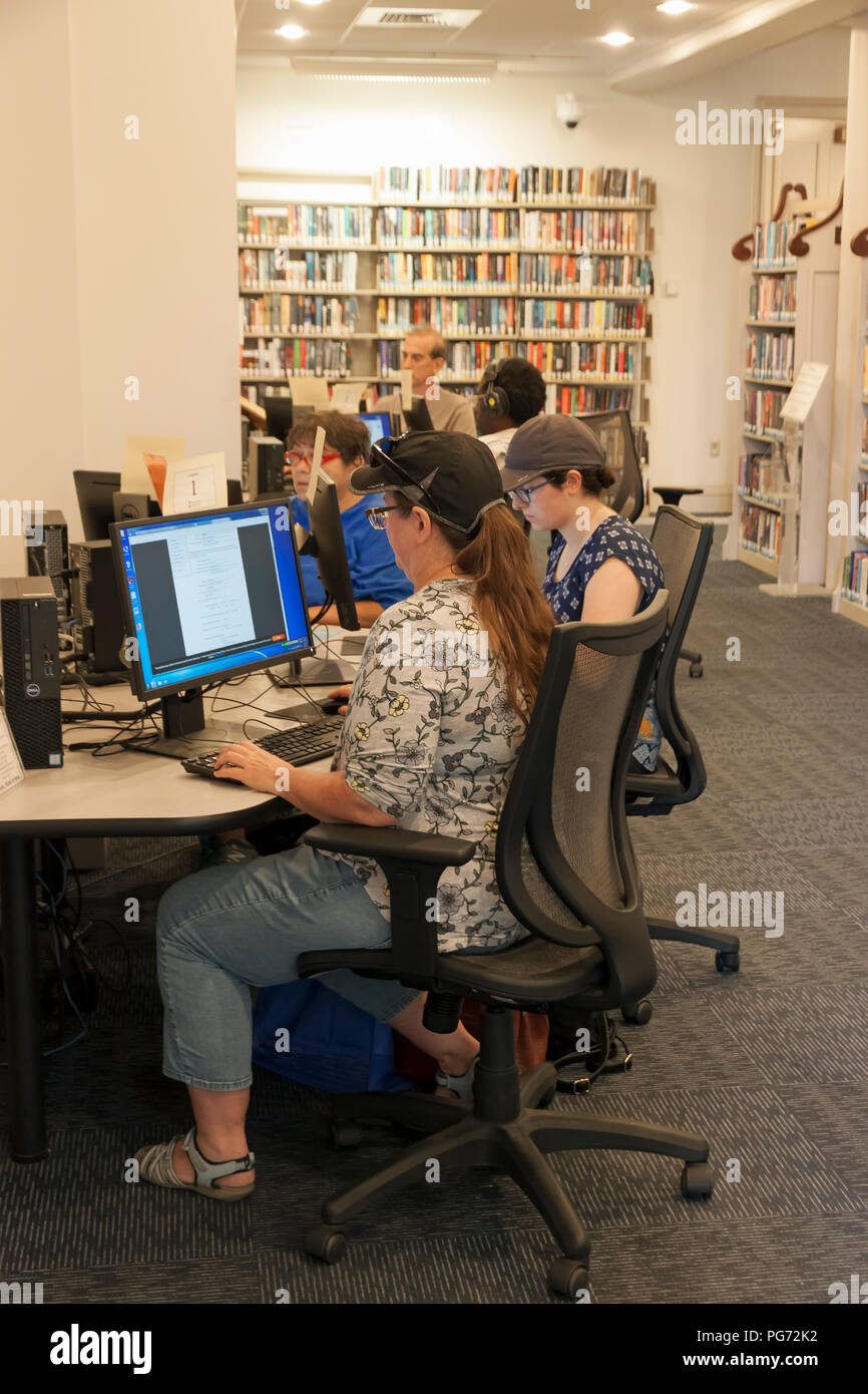 Adults using computers in a public library. - Stock Image