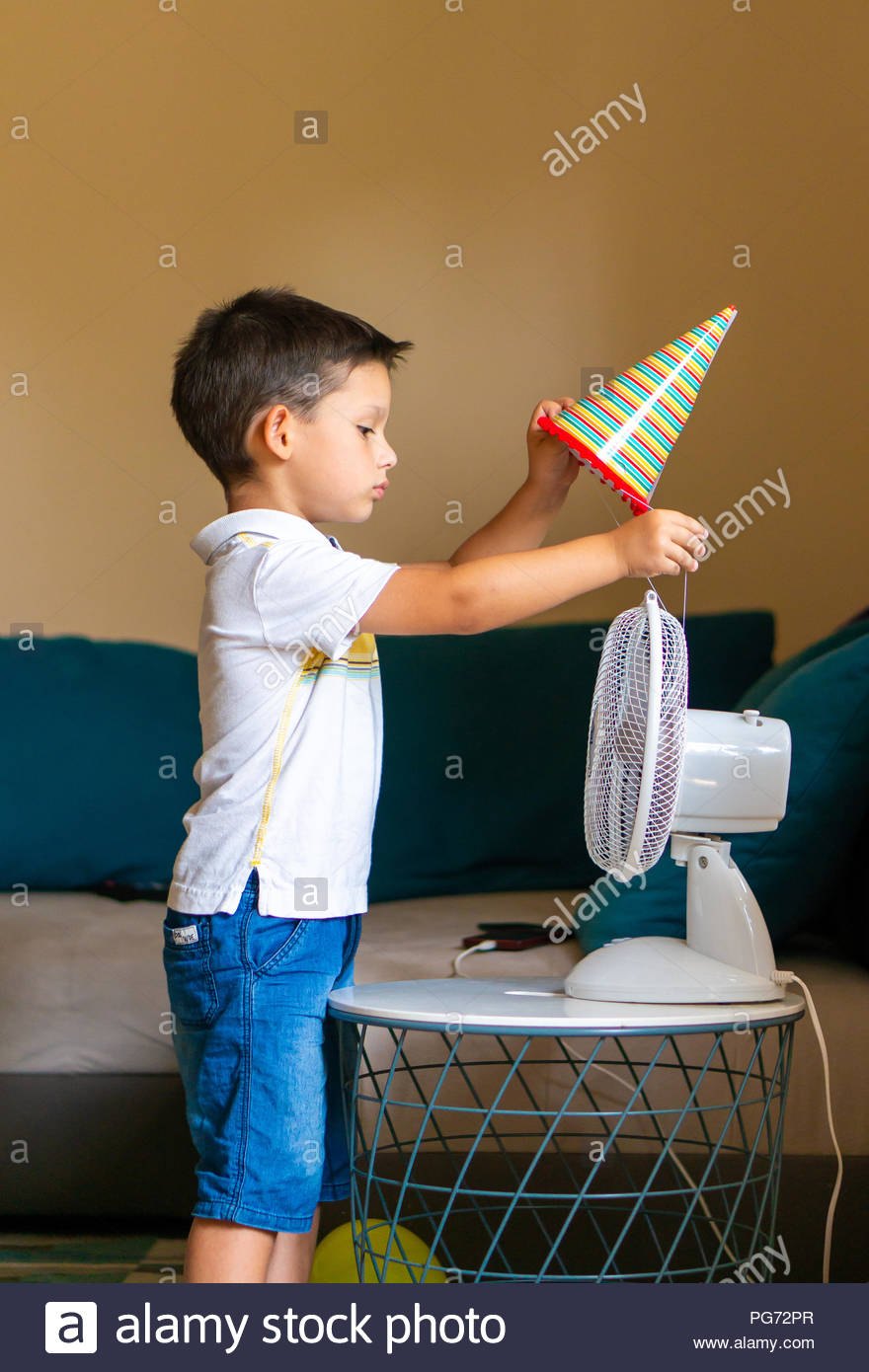 c836d9ab Young boy trying to put a birthday paper hat on a ventilator in a room