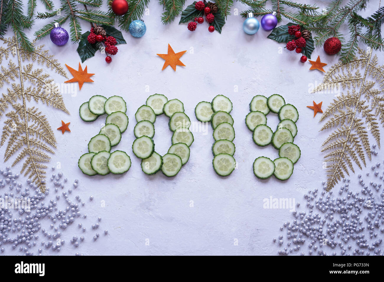 New Year's collage, healthy lifestyle, figures from cucumber, spruce branches, traditional Christmas holiday - Stock Image