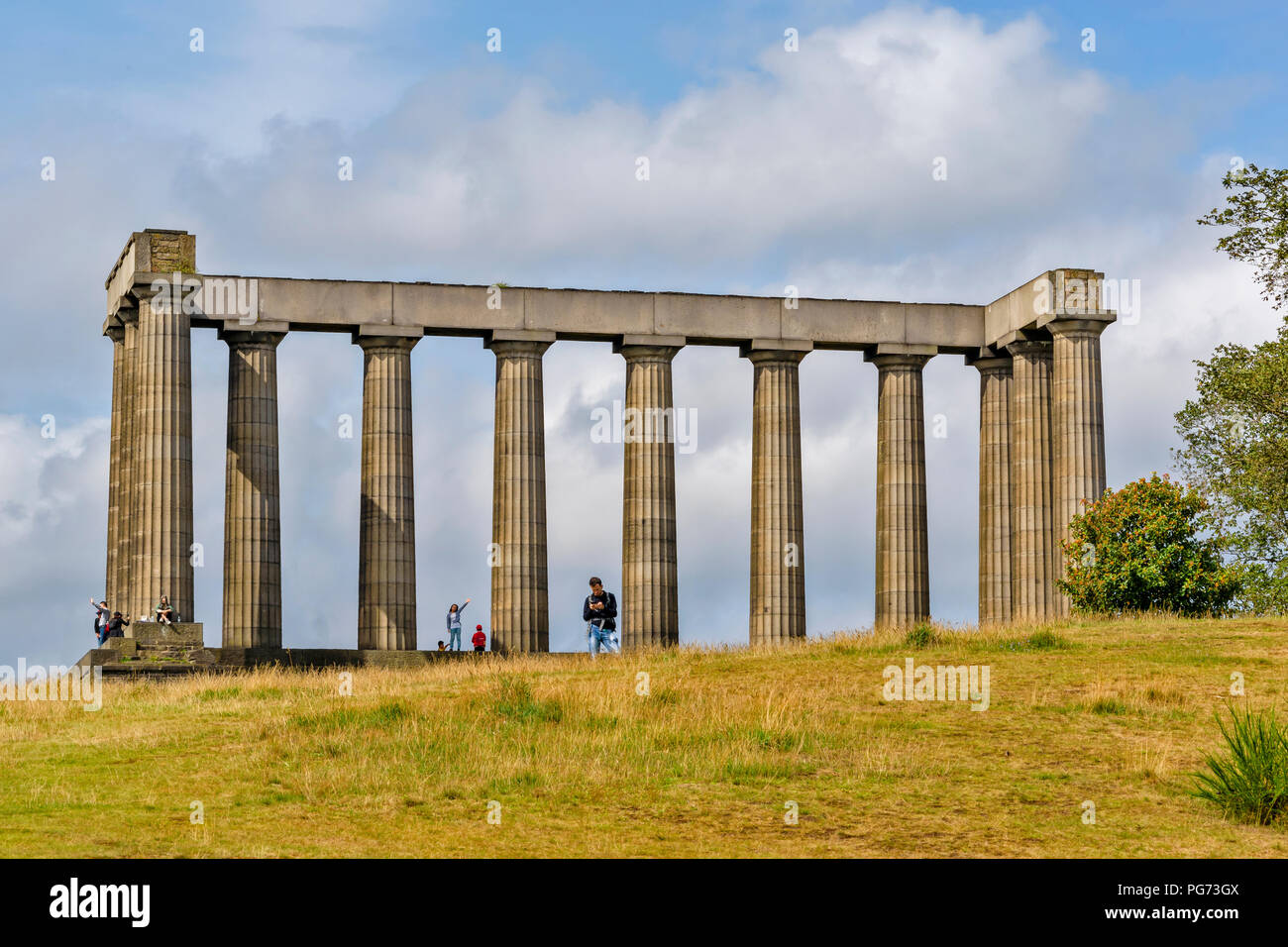 EDINBURGH SCOTLAND CALTON HILL THE NATIONAL MONUMENT OR ACROPOLIS AND TOURISTS IN SUMMER - Stock Image