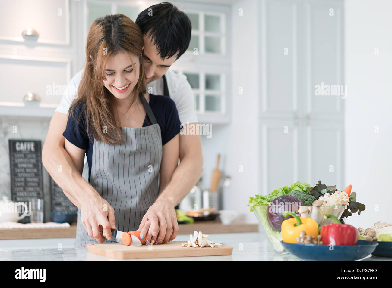 Young beautiful couple in kitchen. Family of two preparing food. Couple making delicious salad. Cooking hobby lifestyle concept. - Stock Image