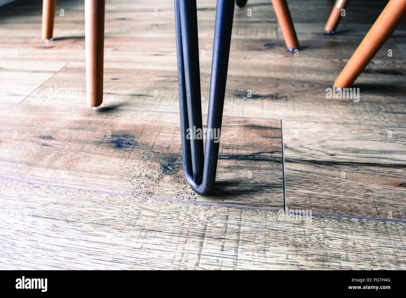 Eiffel style chair leg, in a modern living space - with wooden laminate flooring. - Stock Image