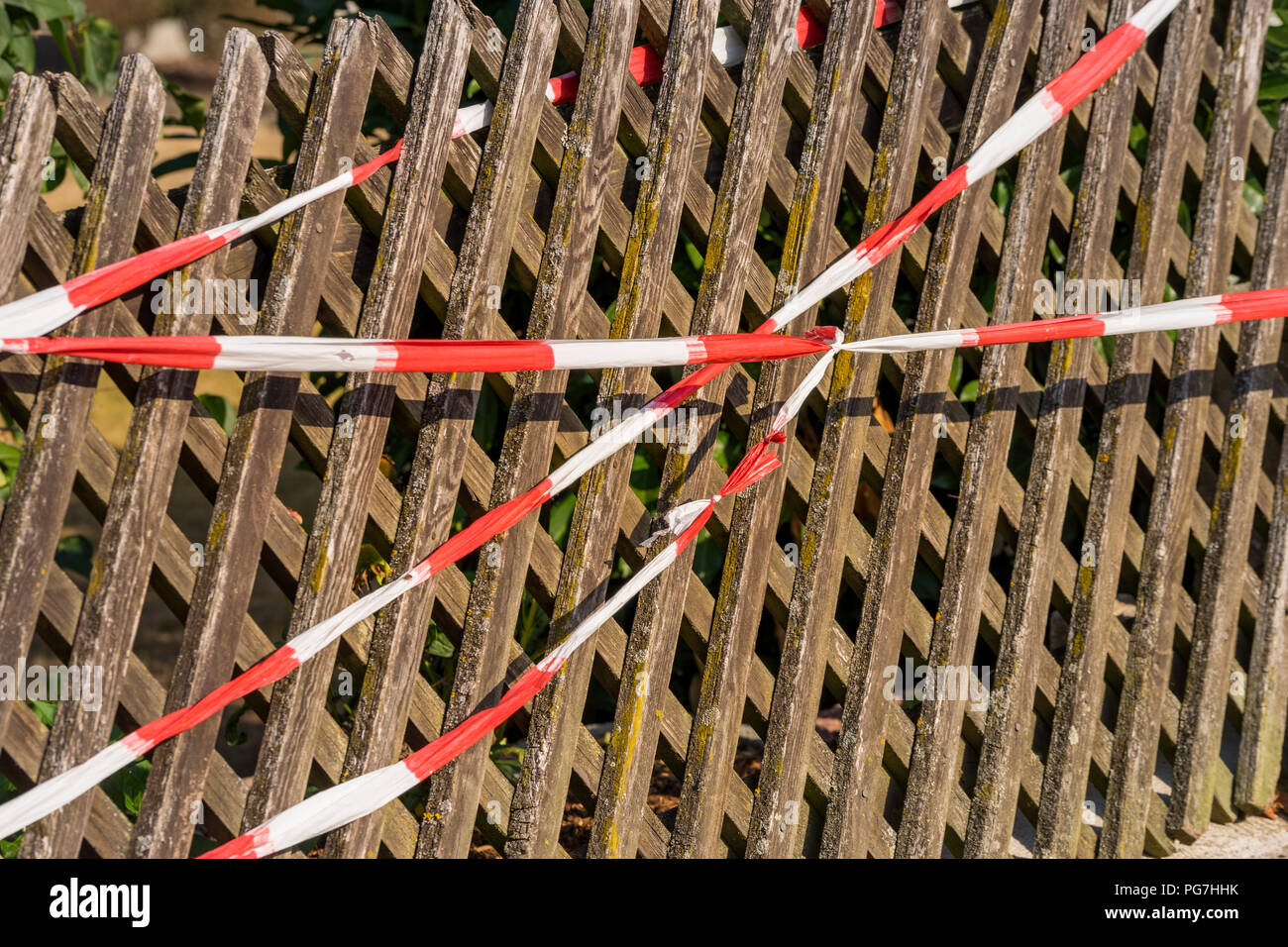 Red and white ribbon barriers at the wooden fence - Stock Image