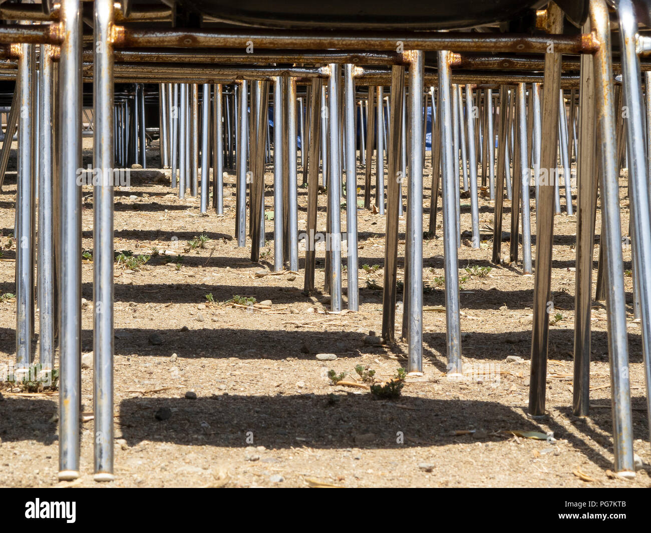 Calabria (Italy): the metal legs of plastic chairs, seen from below, placed in an outdoor theater waiting for the public - Stock Image
