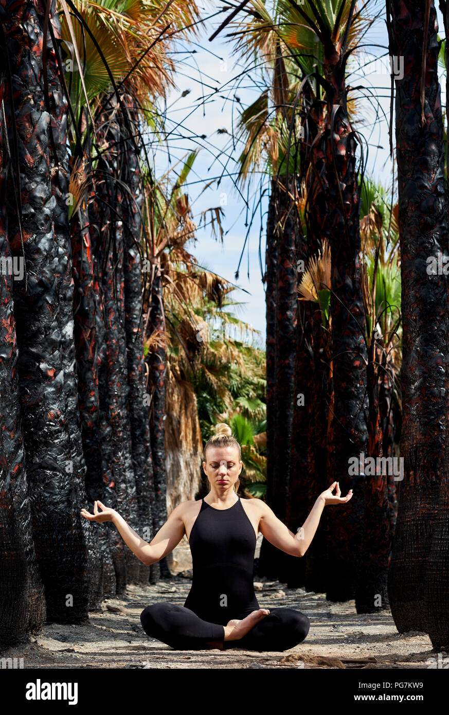 Young woman in black sportswear sitting in lotus position and meditating outdoors. Woman in early gestation. Pre natal exercising, healthy lifestyle.  - Stock Image
