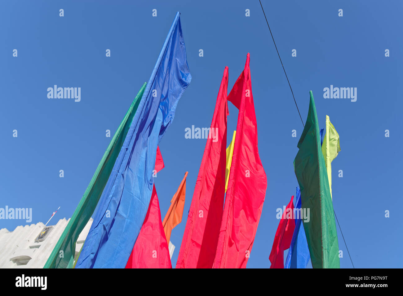Colorful flags against clear blue sky in the city Khabarovsk, Russia - Stock Image