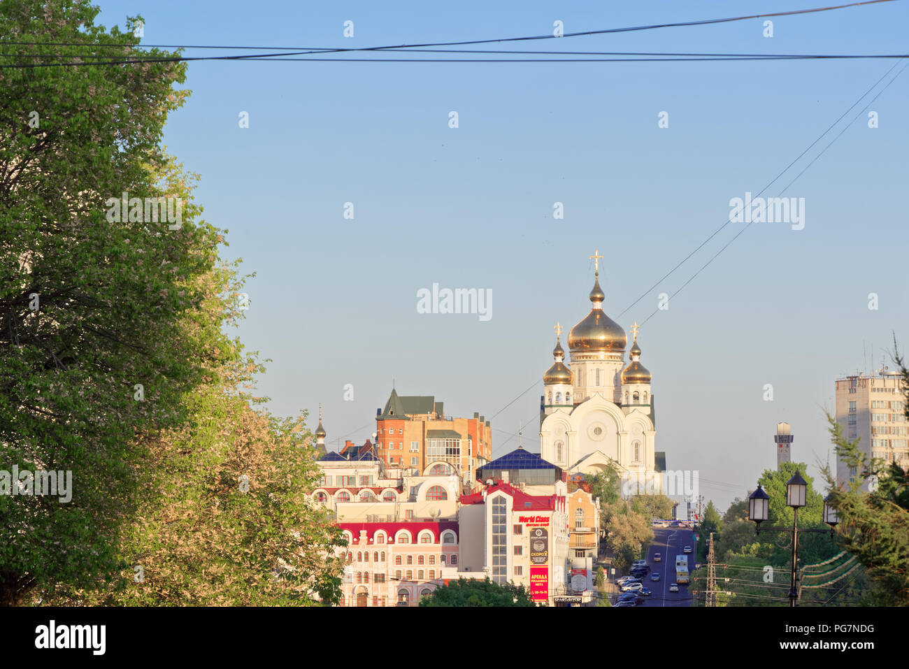 Khabarovsk, Russia - May 29, 2018: View to the russian orthodox church with golden roofs (cupola) and residential buildings in the distant. - Stock Image