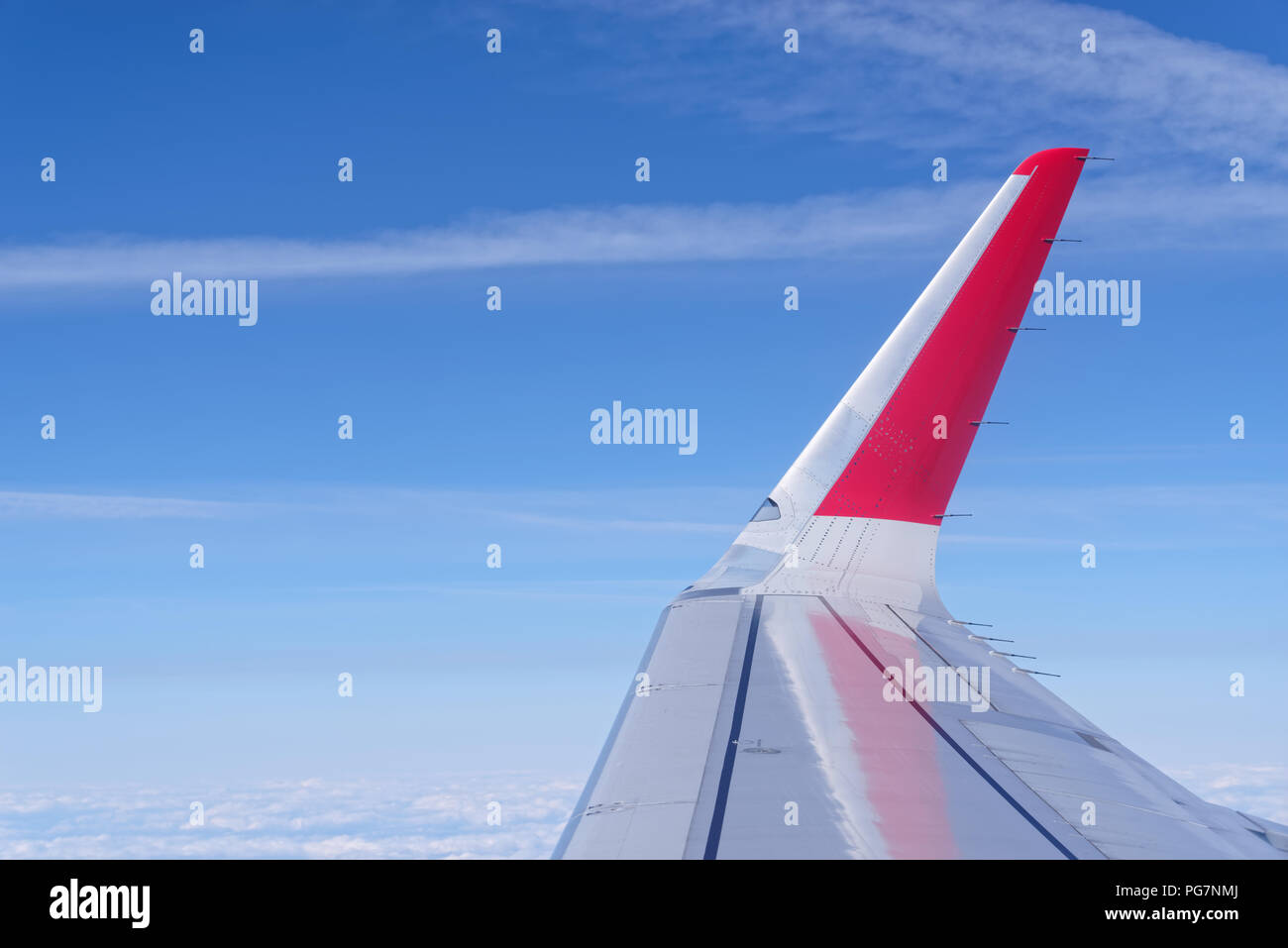 Airplane wing with red colored winglet against blue sky. View from porthole - Stock Image