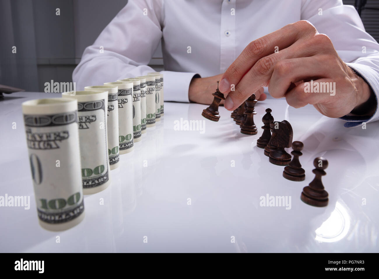 Businessperson Making First Move With Chess Piece Against Rolled Up Banknotes Stock Photo