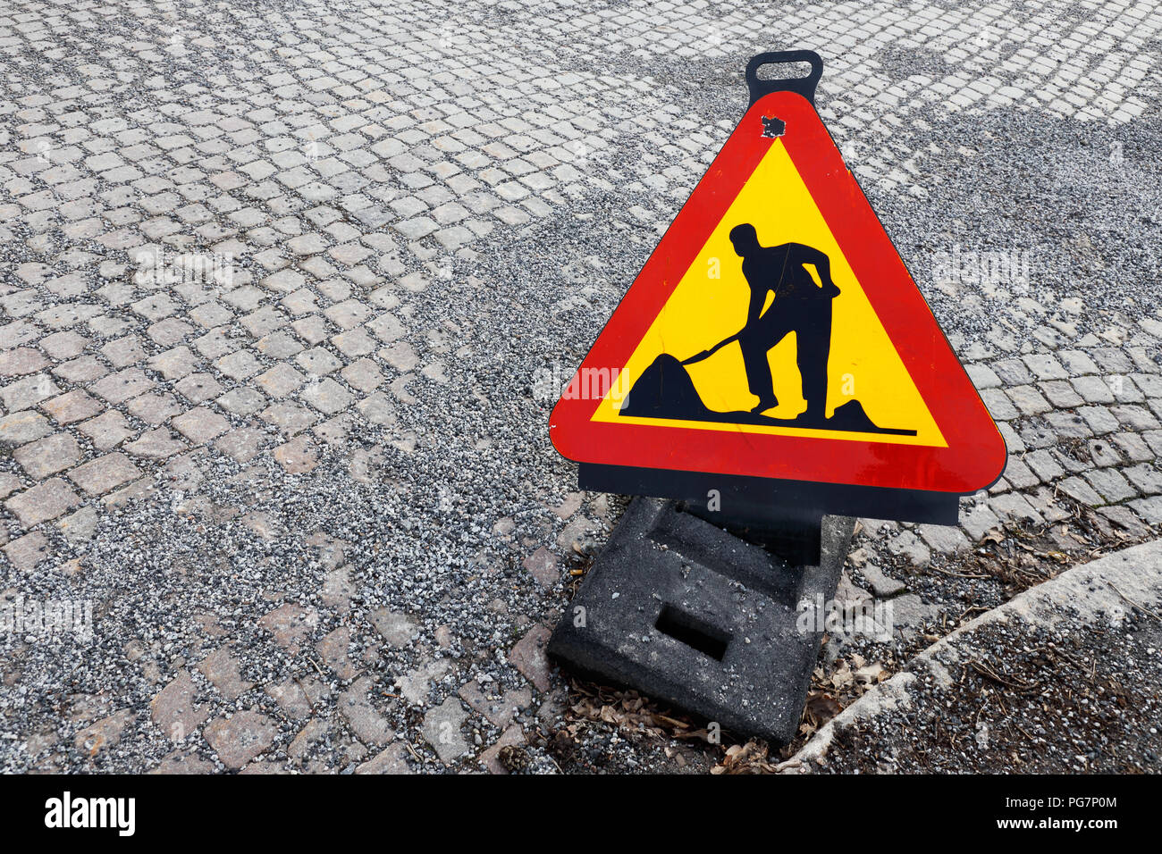 High angel view of a triangle shaped temporary roadwork warning sign placed on a street paved with cobbelstones with gravel on top. - Stock Image