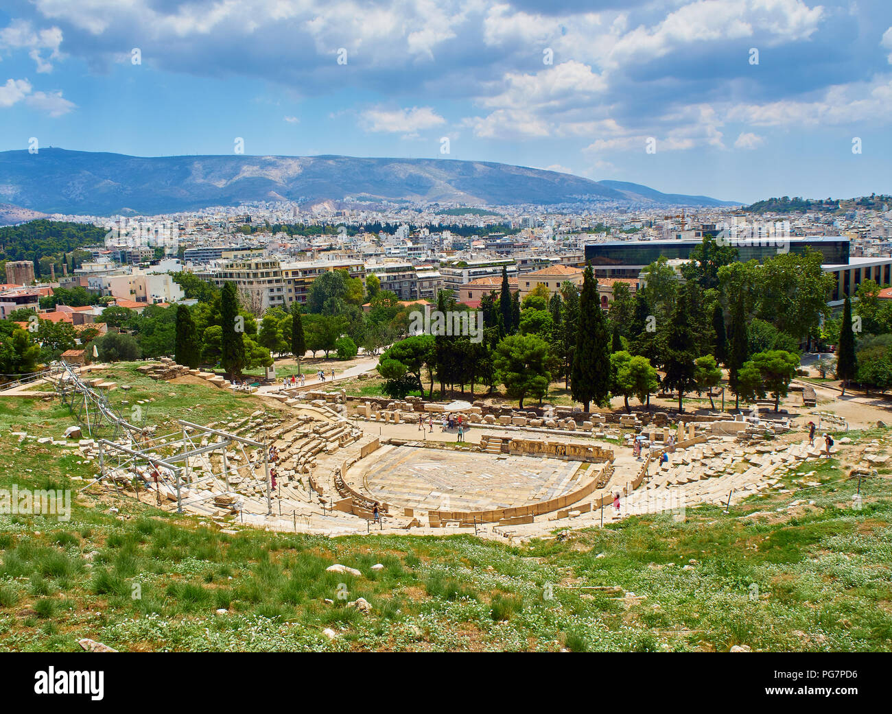 Theatre of Dionysus Eleuthereus on the south slope of the Athenian Acropolis, with the city of Athens in background. Attica region, Greece. - Stock Image