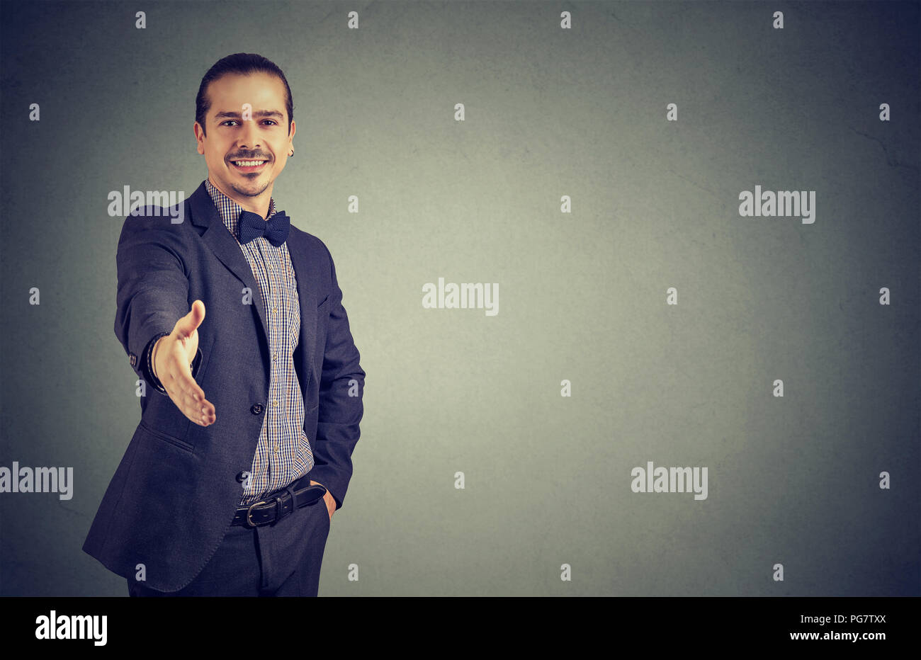 Smiling stylish young man outstretching hand at camera to give greeting handshake on gray - Stock Image
