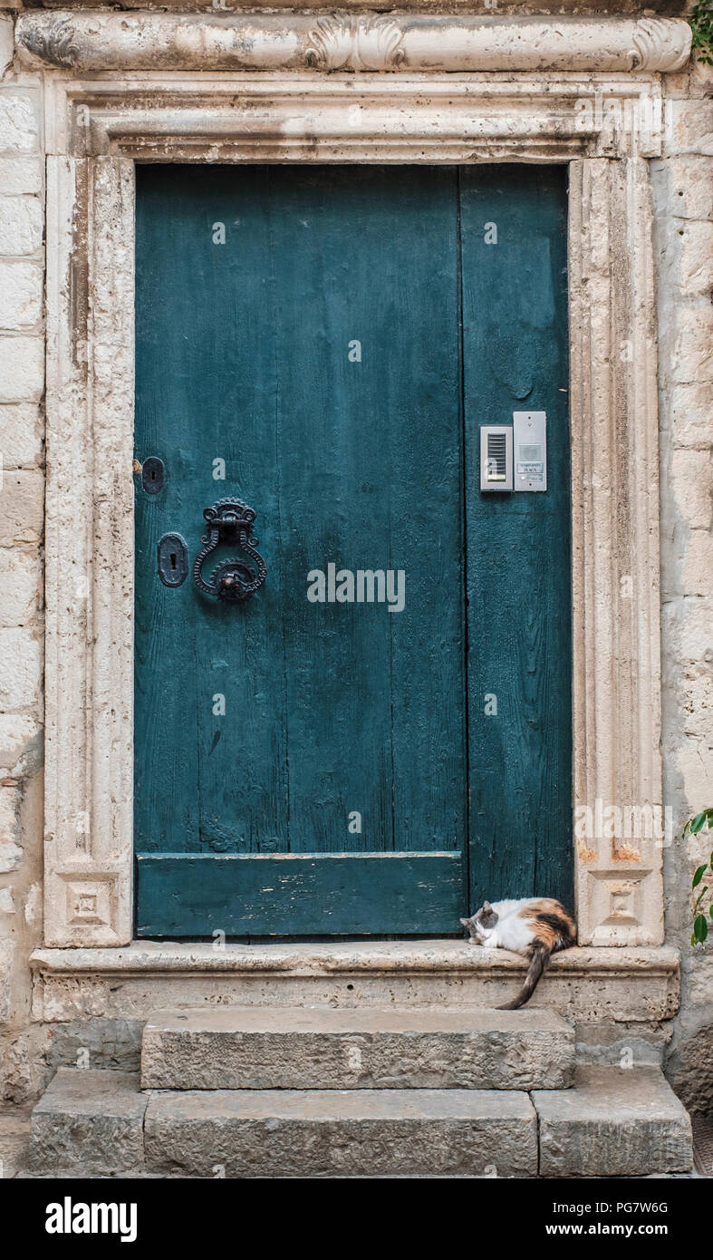 A cat snoozes on a doorstep in the Old Town, Dubrovnik, Croatia, Europe - Stock Image
