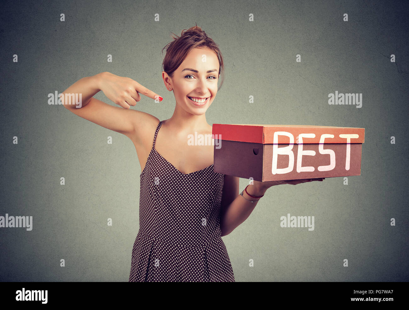 Smiling young saleswoman advertising best product - Stock Image