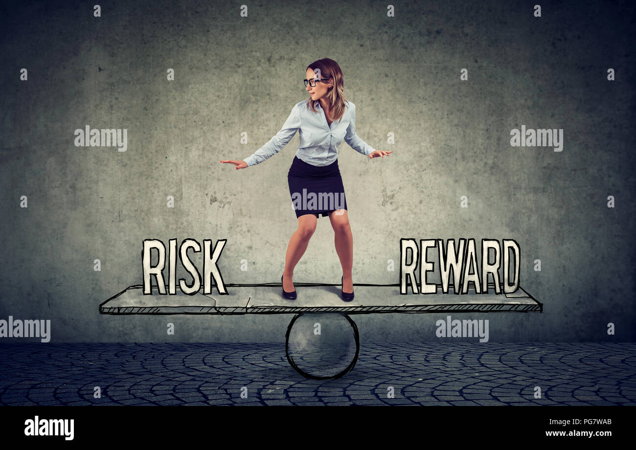 Skillful young business woman balancing between reward and risk in challenging corporate environment - Stock Image