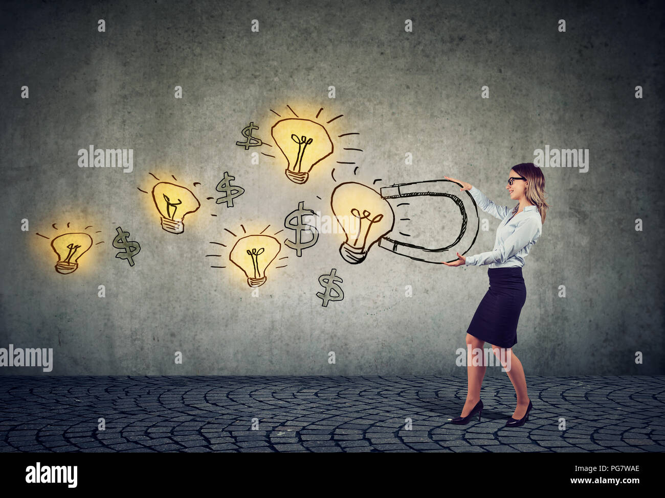 Business woman attracts bright ideas light bulbs with a big magnet - Stock Image