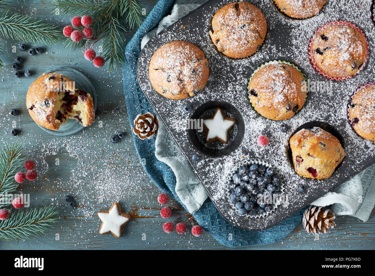 Blueberry muffins with sugar icing in a baking tray with Christmas decorations around, flat lay, view from above - Stock Image