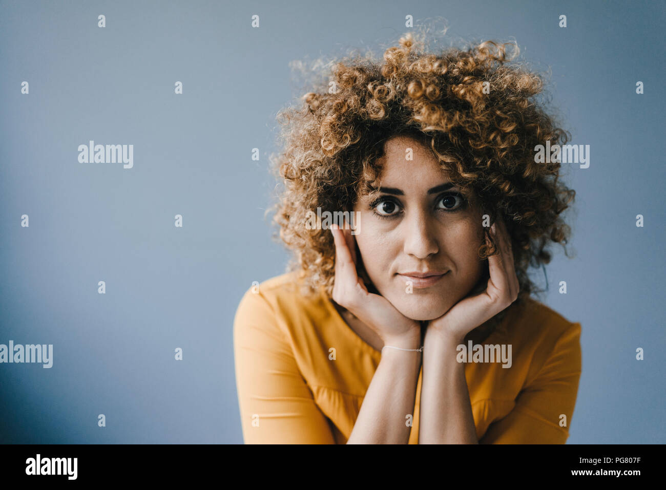 Portrait of woman with head in hands Stock Photo