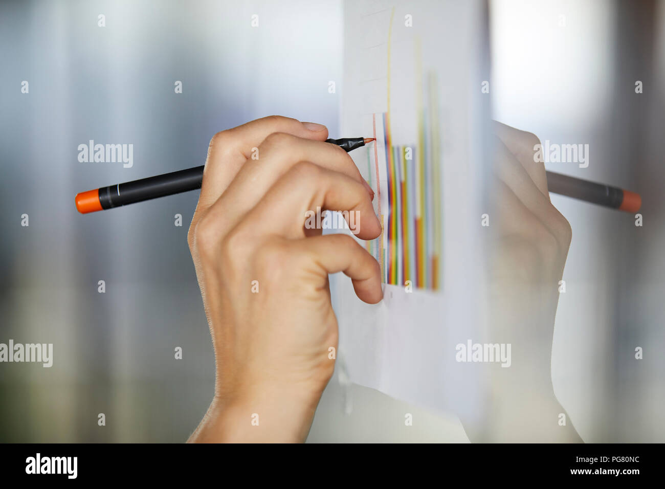 Hand drawing bar charts on paper at glass pane - Stock Image