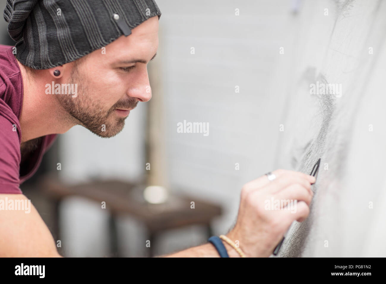 Focused artist drawing on canvas - Stock Image