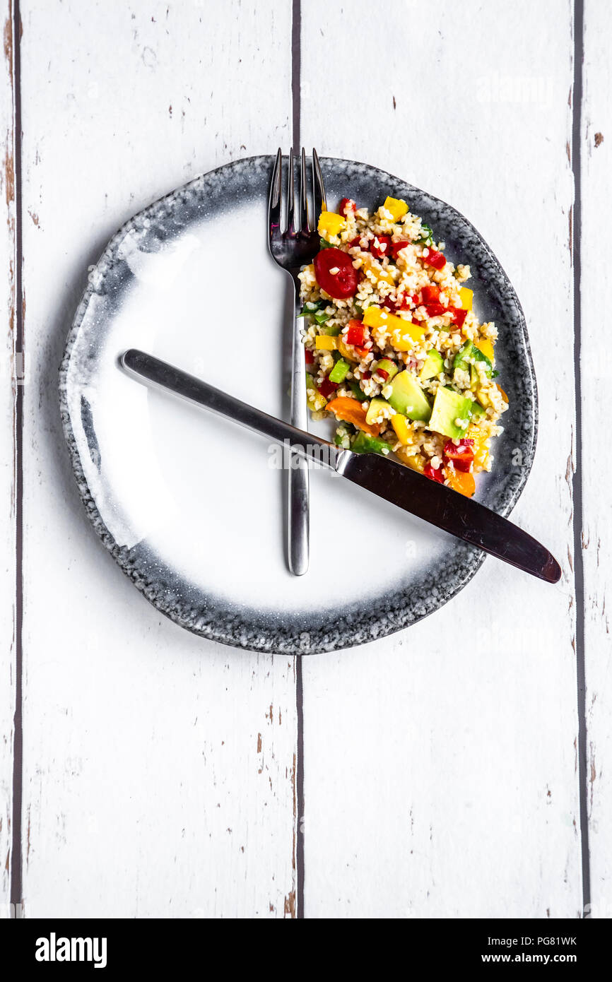 Bulgar salad on round plate, symbol for intermittent  fasting Stock Photo