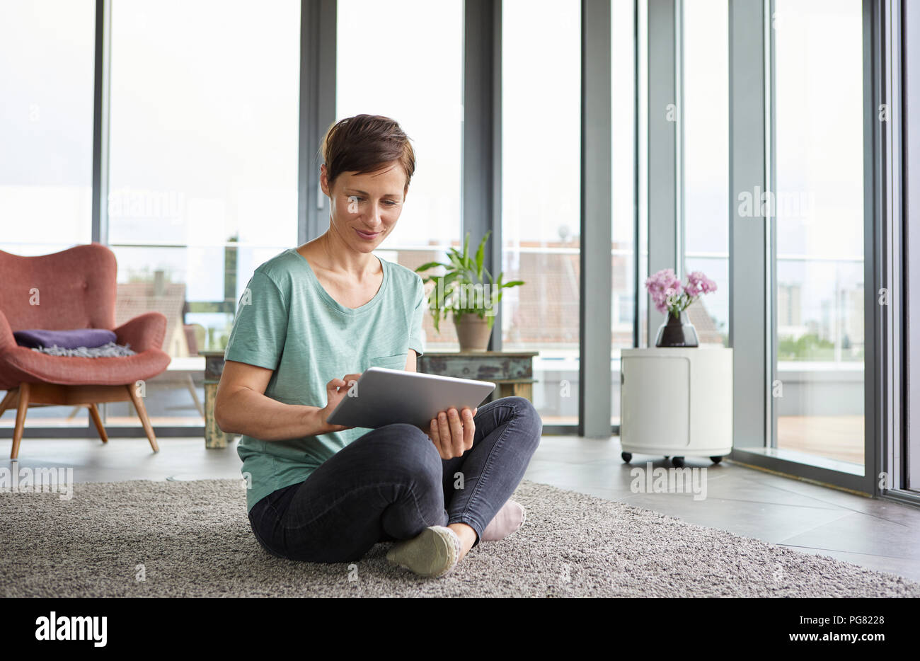 Woman sitting on the floor at home using tablet - Stock Image