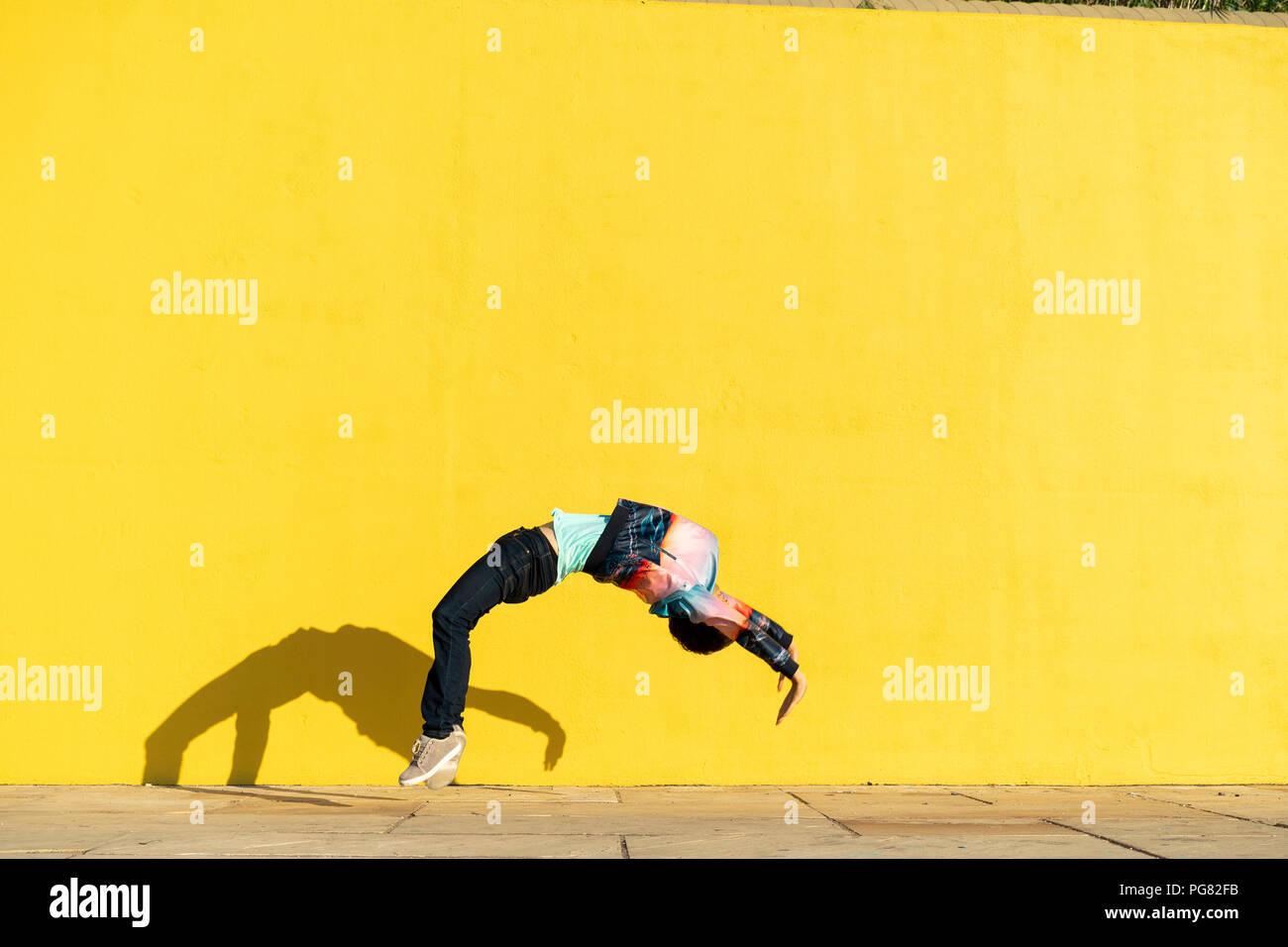 Acrobat jumping somersaults in front of yellow wall Stock Photo