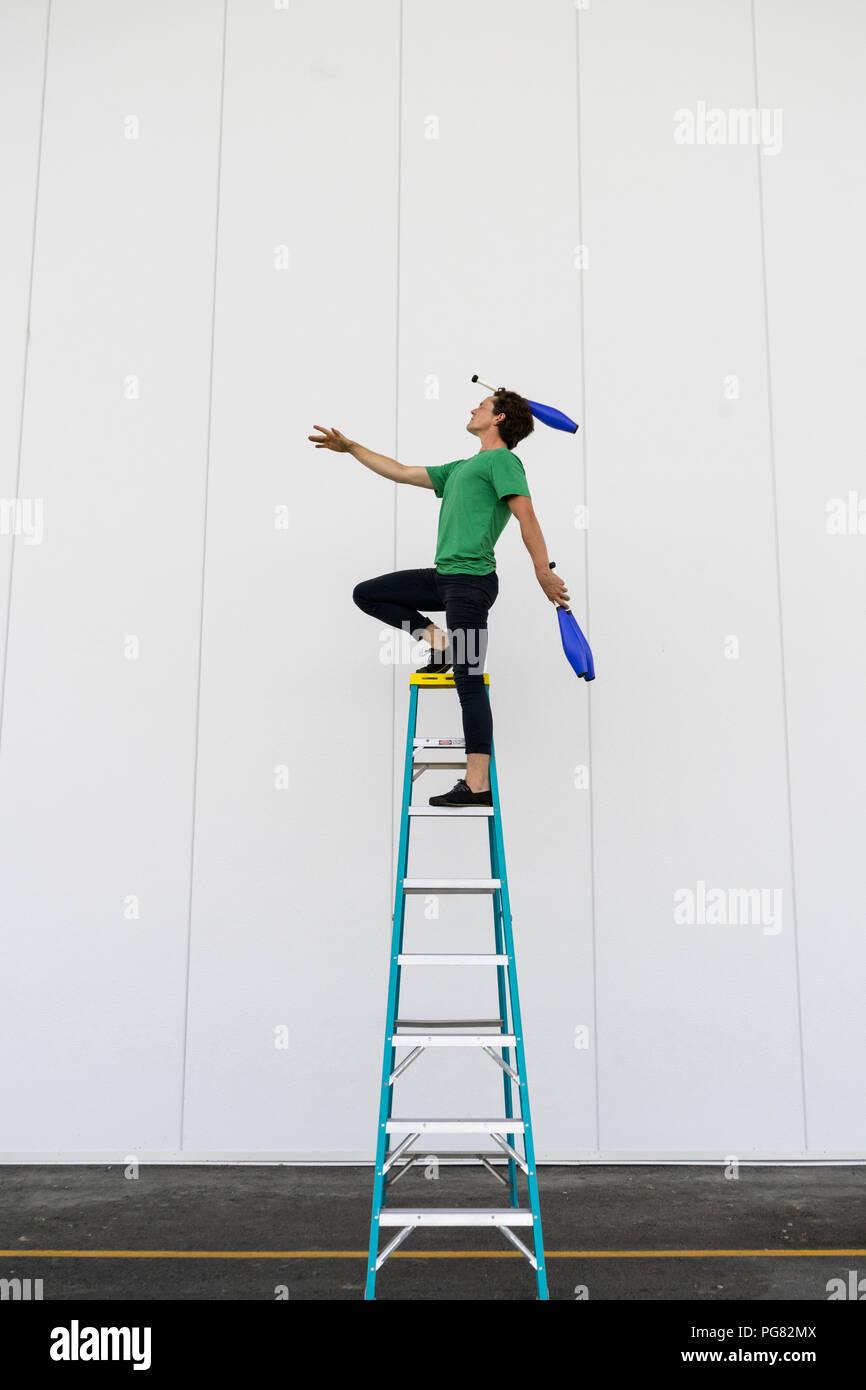 Acrobat standing on ladder, juggling - Stock Image