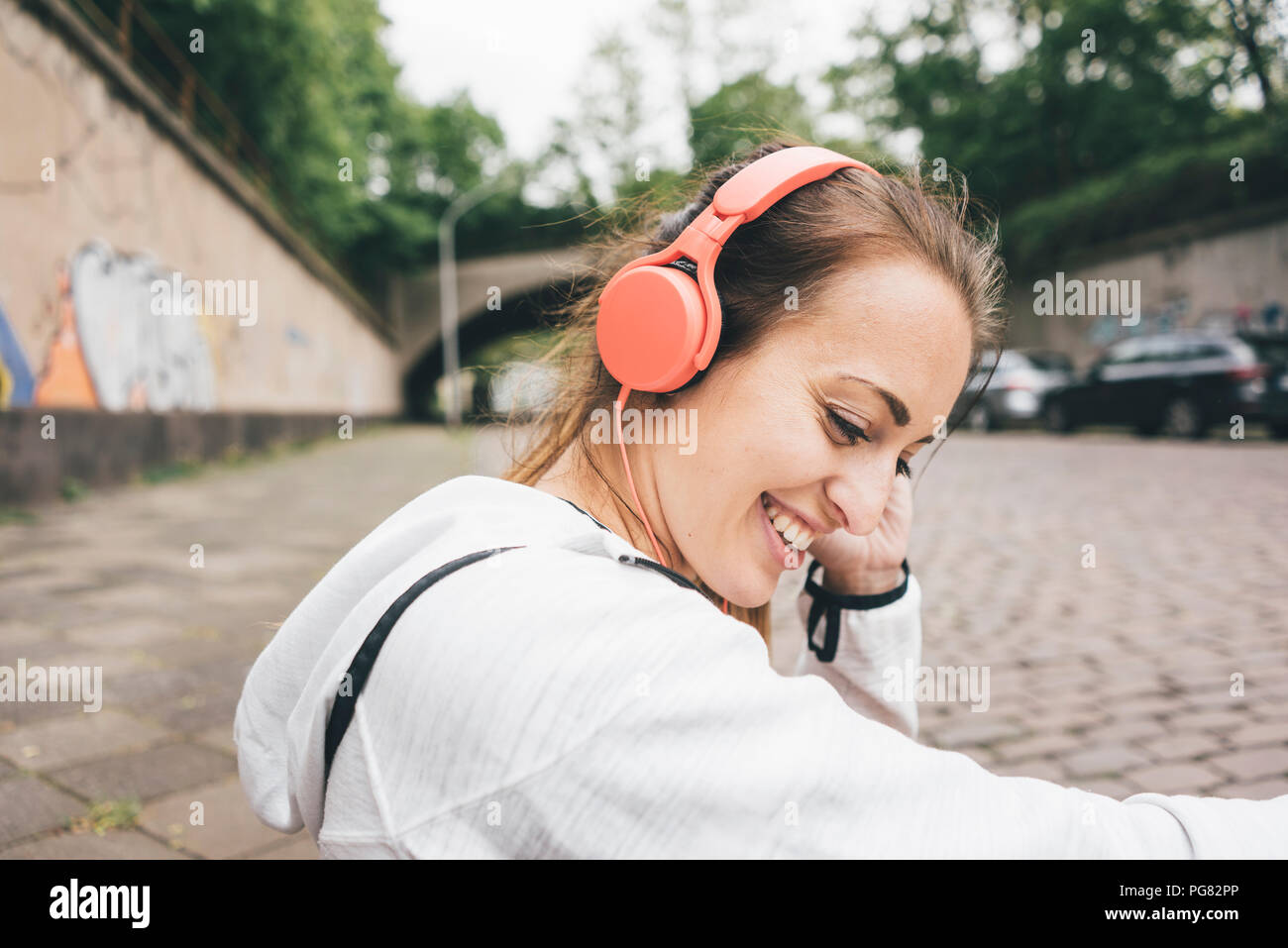 Smiling sportive young woman wearing headphones outdoors - Stock Image