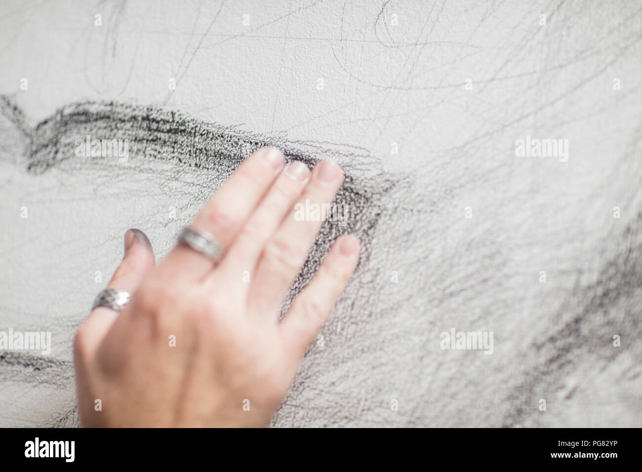 Artist's hand touching drawing - Stock Image