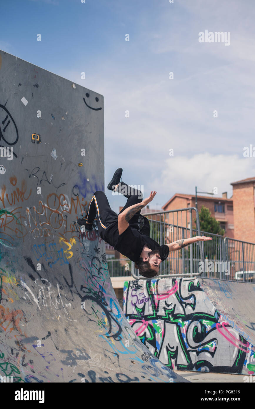 Tattooed man doing parkour in a skatepark - Stock Image