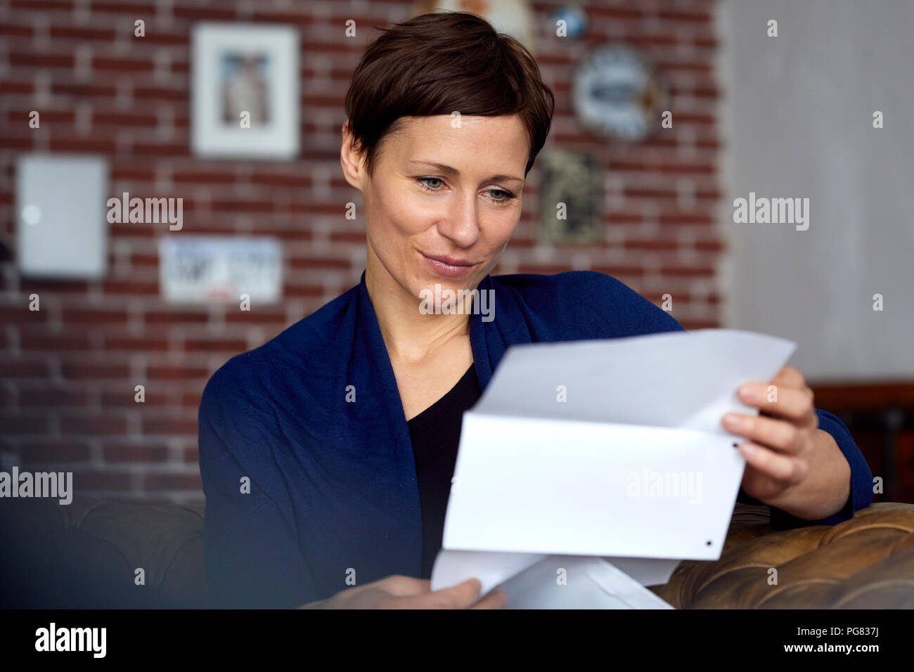 Woman reading letter at home - Stock Image