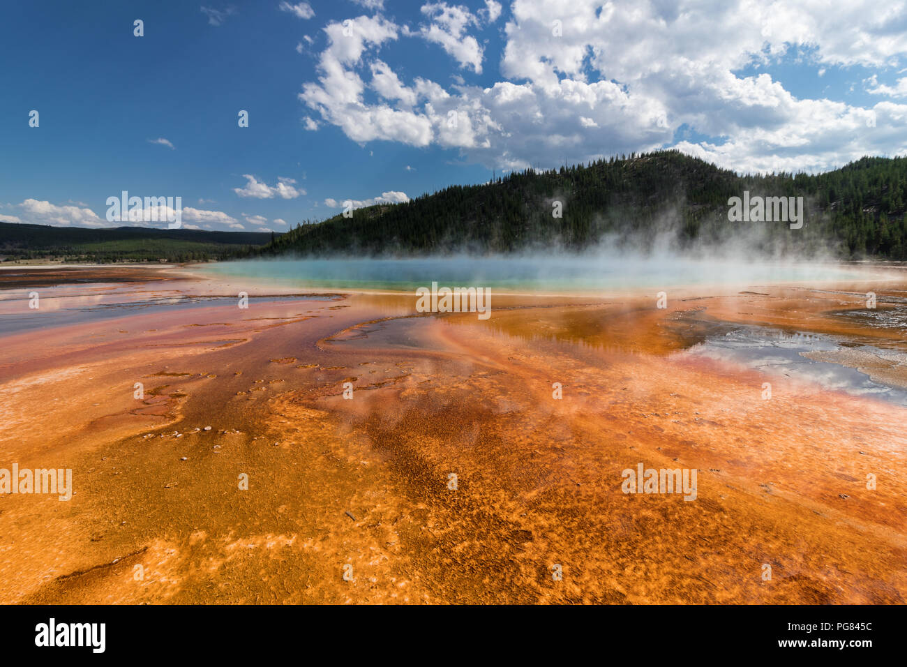 Grand Prismatic Spring - Yellowstone Park. Landscape on a Summer sunny day with clouds. Contrast of colors - Orange, Green Blue Stock Photo