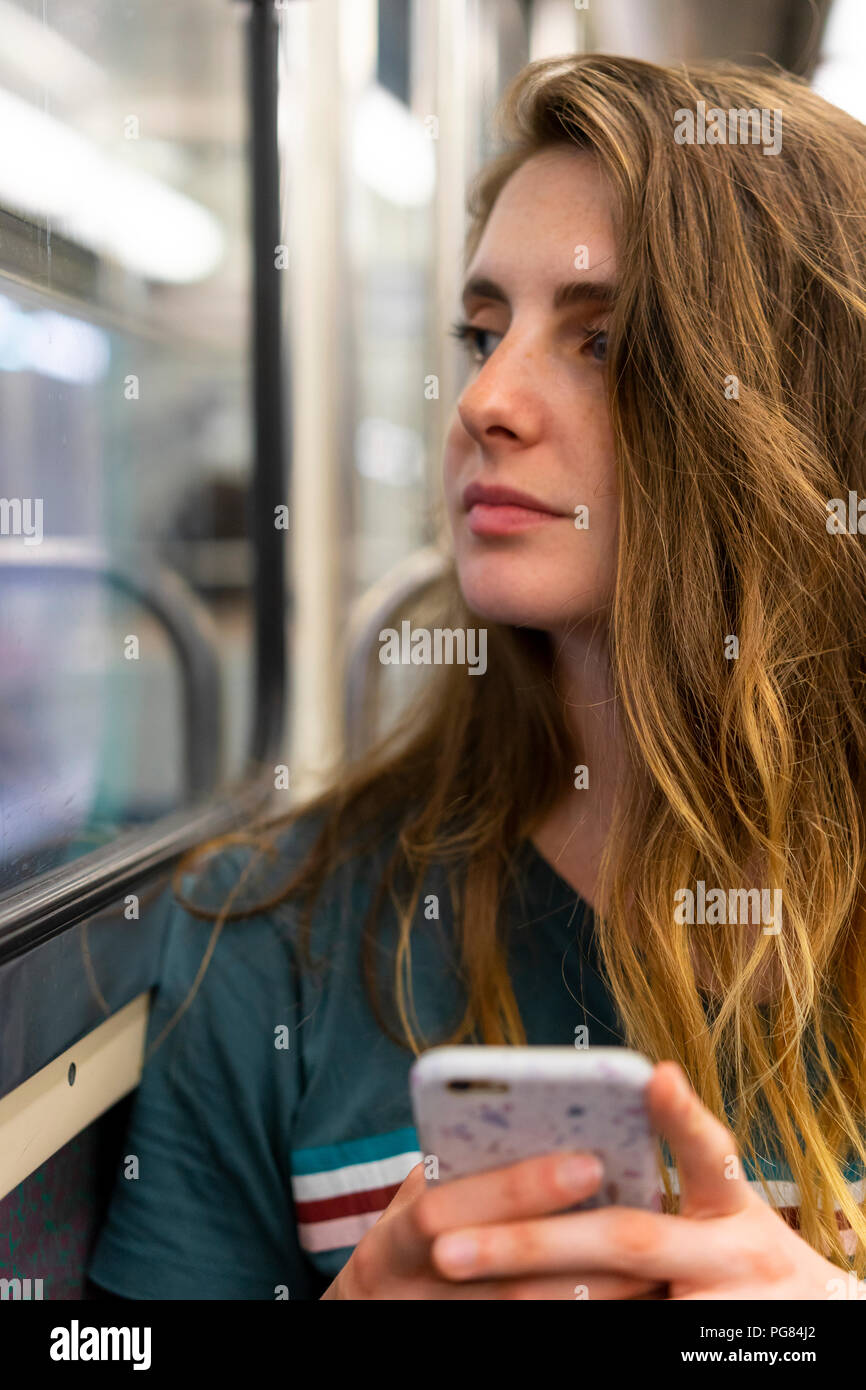 Portrait of young woman with smartphone in underground train - Stock Image