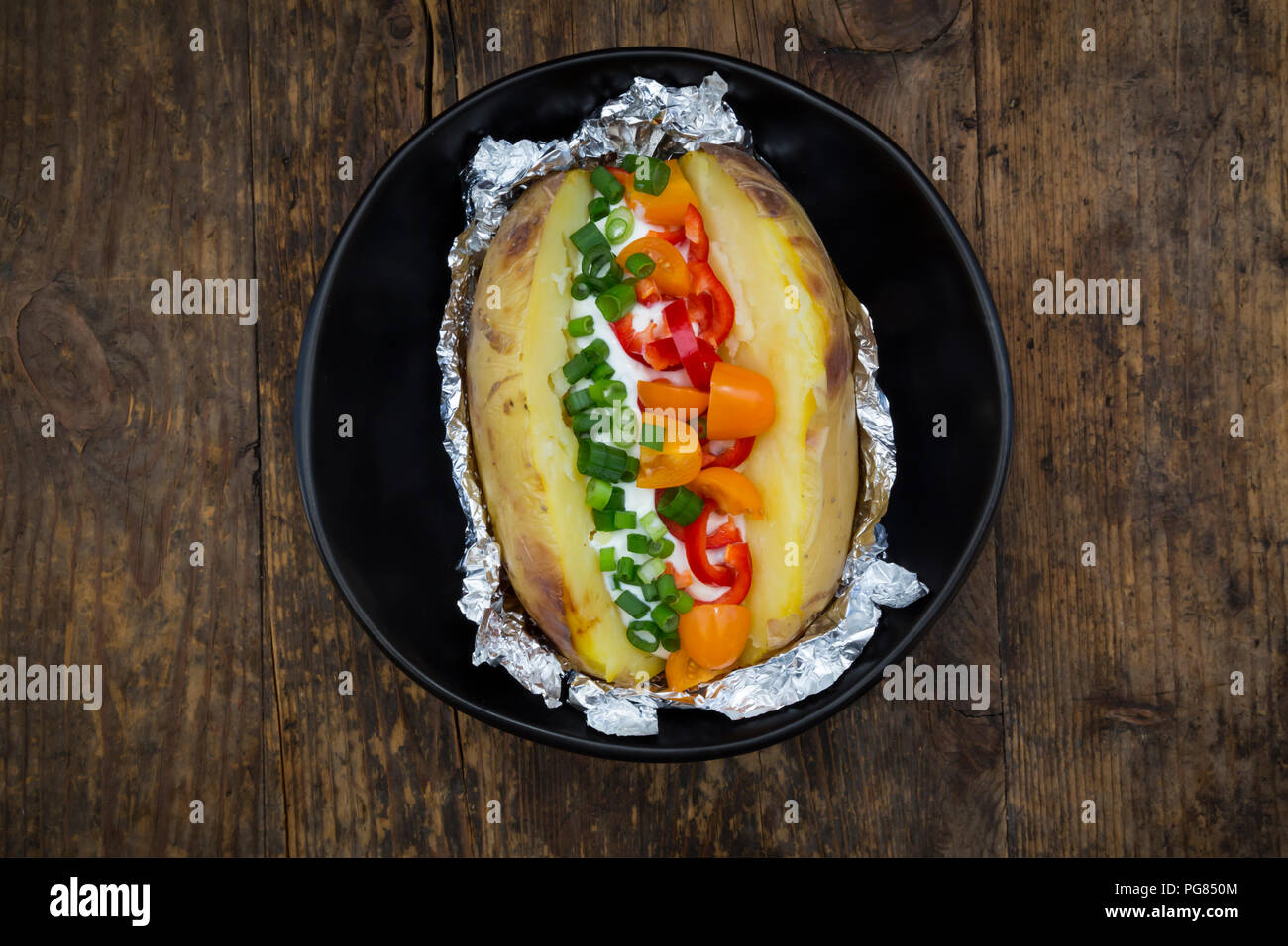 Baked patato with curd and chives, bell pepper, tomato and spring onions - Stock Image