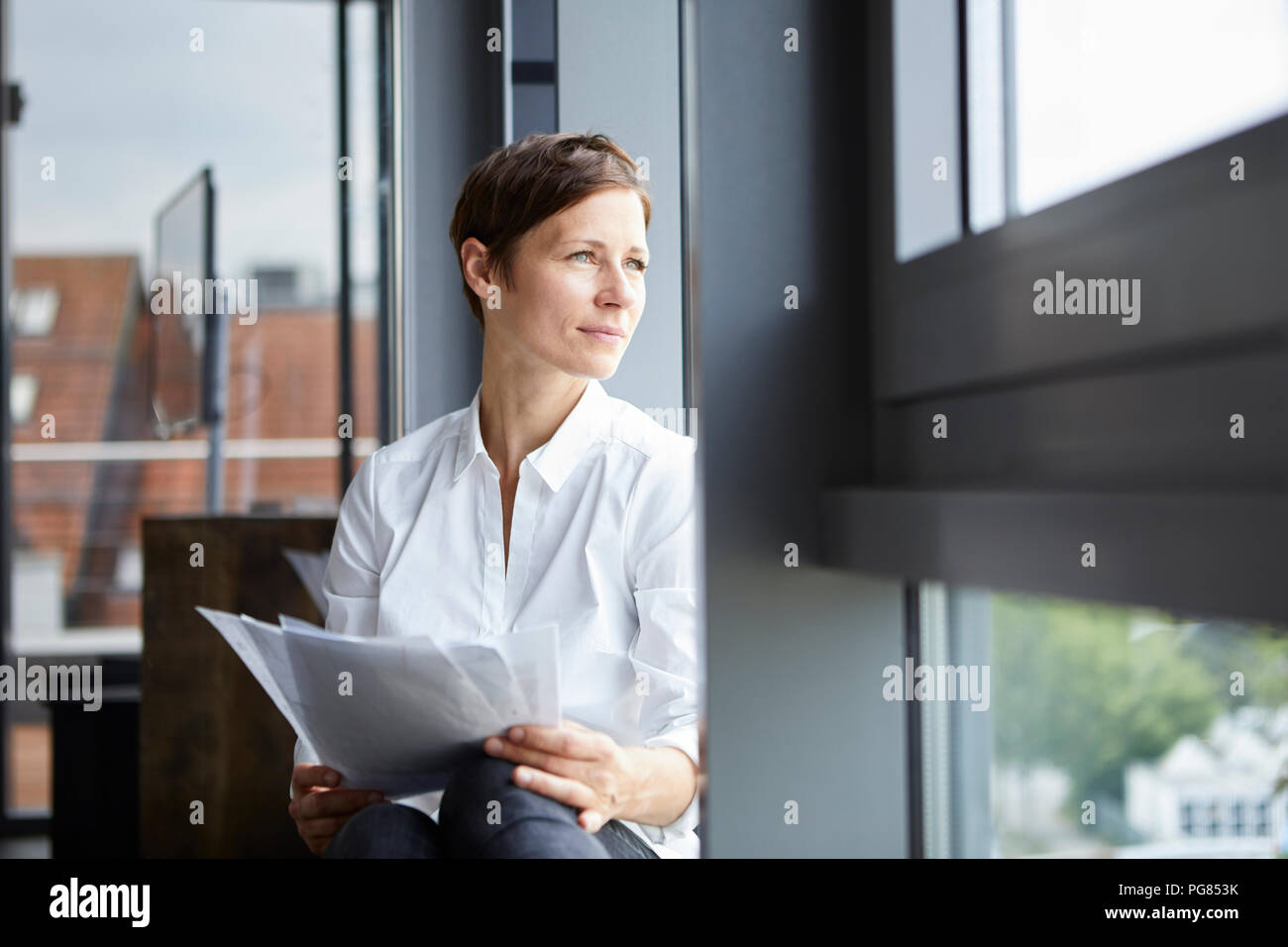 Businesswoman sitting in office with documents looking out of window - Stock Image