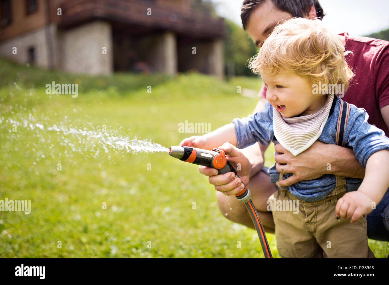 Little boy with his father watering the lawn - Stock Image