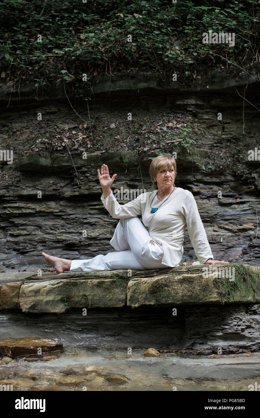 Senior woman doing yoga on rock, Half-spinal twist - Stock Image
