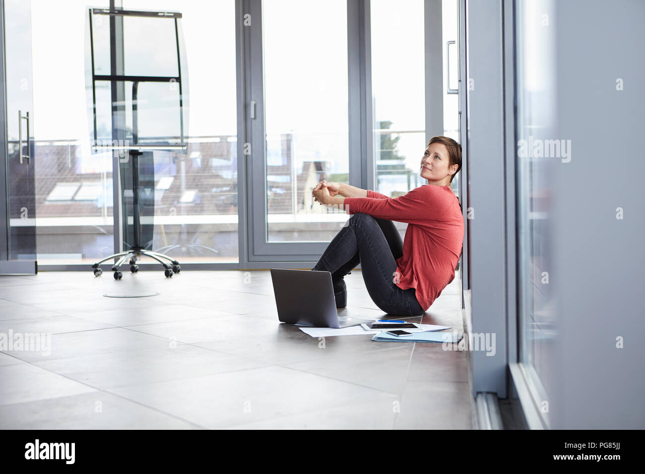 Businesswoman sitting on the floor in office with laptop and documents - Stock Image