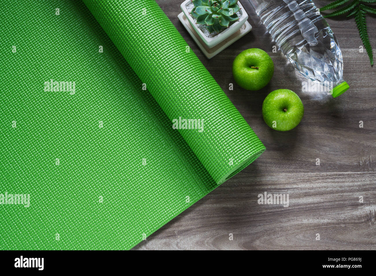 f84de9ba78ffa Green yoga mat on a wooden background with green apples and bottle of  water. Active healthy lifestyle background concept.