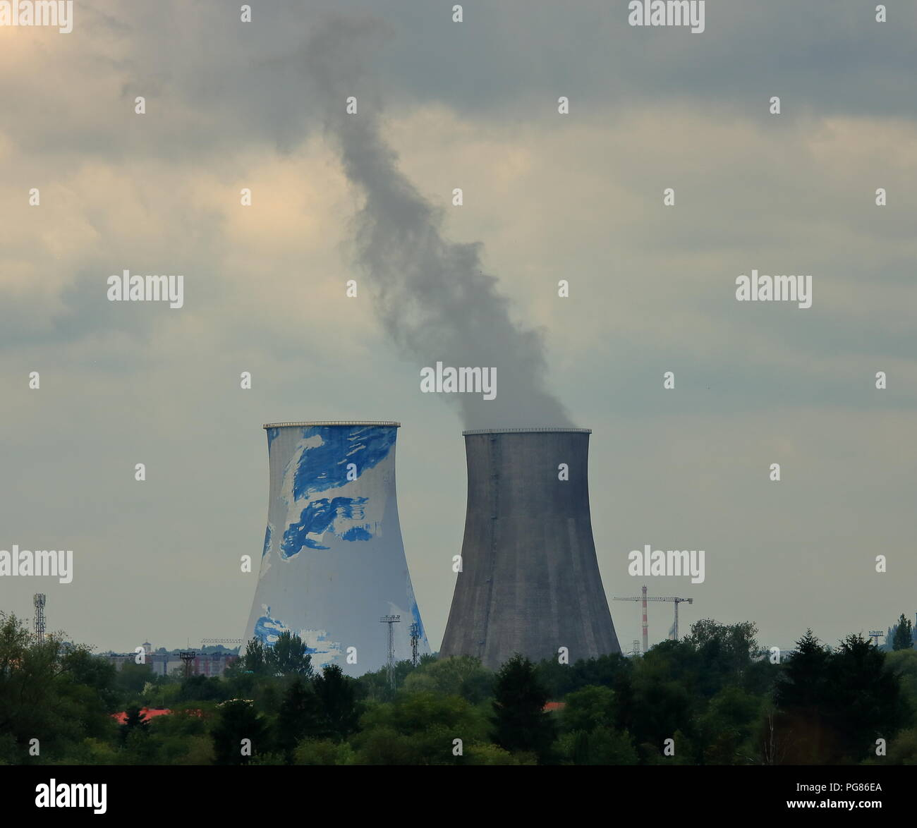 Two big chimneys of refinrey (factory), from one of them up in smoke, cloudy sky., - Stock Image