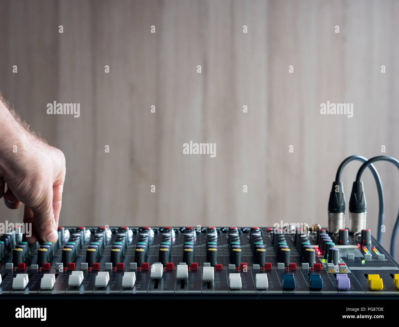 Adjusting buttons on audio mixer in music studio - Stock Image