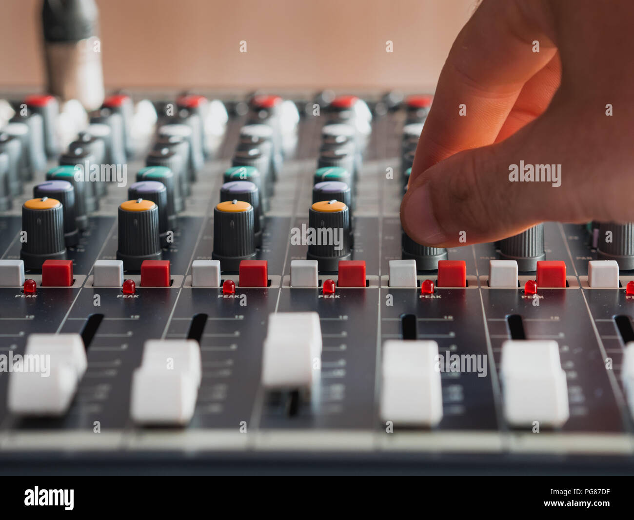 Adjusting buttons on audio mixer in music studio close up - Stock Image
