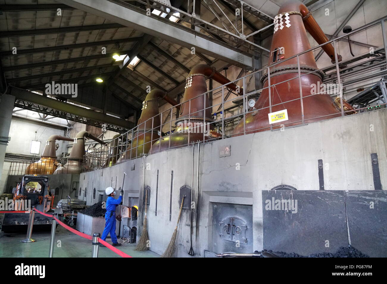 Hokkaido Asahi Beer Factory, Sapporo, Hokkaido, Japan.  A worker putting charcoal into the kiln with the impressive stills looming above. - Stock Image