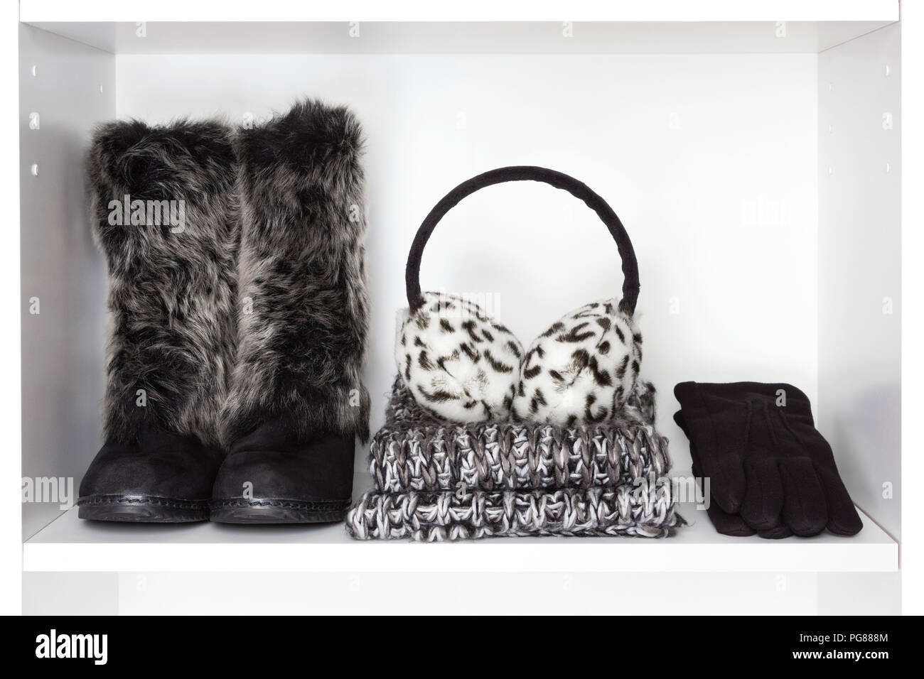 Winter fashion women accessories on white shelf. Faux fur suede boots, knitted scarf, warm earmuffs, black wool gloves - Stock Image