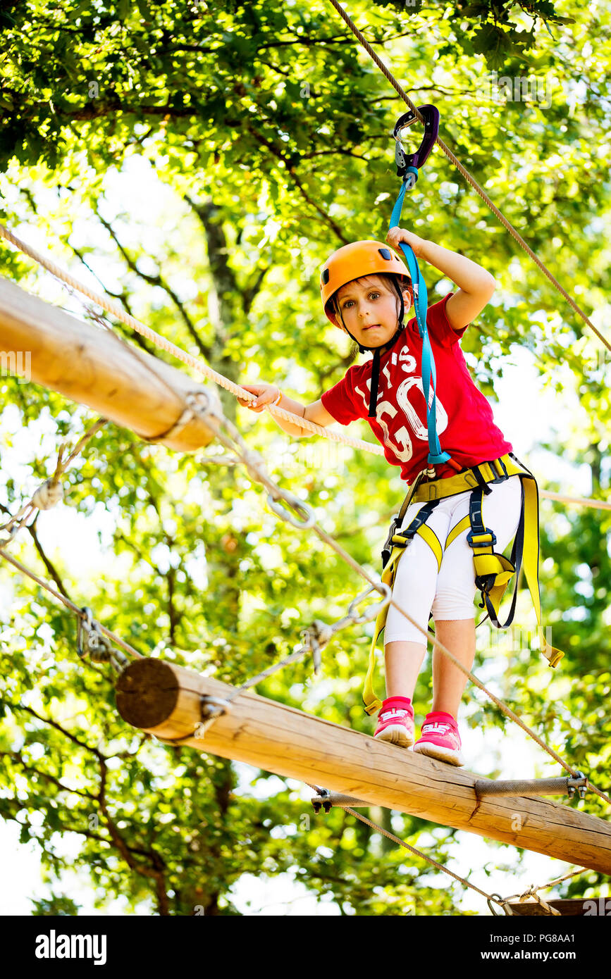 Little brave caucasian girl at outdoor treetop climbing adventure park. 7 years old girlie climbing in a rope playground structure in 5 meters high al Stock Photo